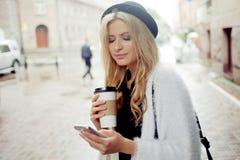 La femme gaie dans le café potable de matin de rue et utilisent son smartphone Image libre de droits