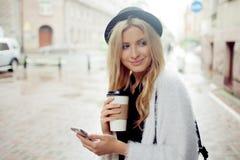 La femme gaie dans le café potable de matin de rue et utilisent son smartphone Photographie stock