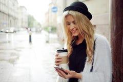 La femme gaie dans le café potable de matin de rue et utilisent son smartphone Photos libres de droits