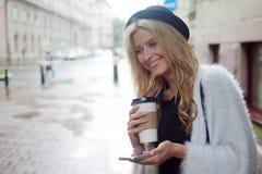 La femme gaie dans le café potable de matin de rue et utilisent son smartphone Images libres de droits