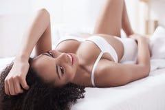 La femme gaie de mulâtre prolifère sur le divan Photographie stock