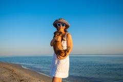La femme gaie en verres d'une manière amusante se tient sur les WI de bord de la mer Image stock