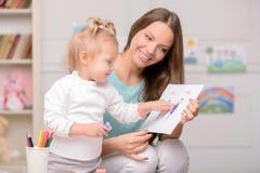 La femme gaie enseigne son enfant à dessiner Images stock