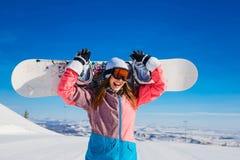 La femme gaie heureuse en costume et verres de ski tient un surf des neiges dans des ses mains en hiver extrême image stock