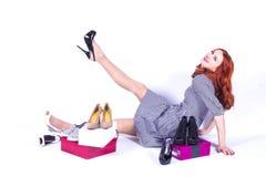 La femme gaie mesure les chaussures Photographie stock libre de droits
