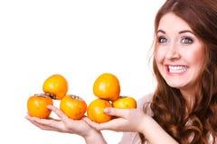 La femme gaie tient des fruits de kaki de kaki, d'isolement Photo stock