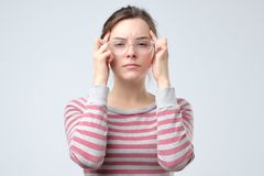 La femme garde des doigts sur des temples concept de migraine photo stock