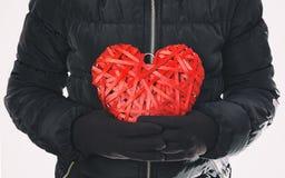 La femme garde en avant le cadeau, coeur en osier rouge Photo libre de droits