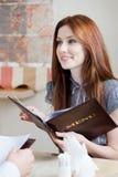 La femme garde la carte pour effectuer une commande Photographie stock