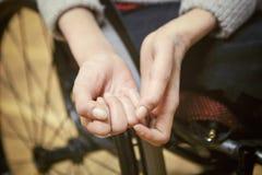 La femme handicapée sur un fauteuil roulant juge sa main fermée Photo libre de droits