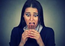 La femme hantée a fatigué des restrictions de régime implorant le chocolat de bonbons Photos stock