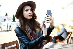 La femme heureuse à l'aide des comprimés numériques tout en se reposant dans le restaurant, font la photo de selfie Photo stock