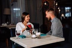 La femme heureuse étonnée s'asseyant par la table la date en café et obtient le cadeau Photographie stock libre de droits
