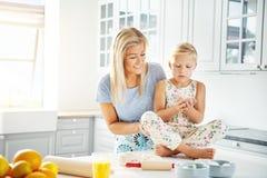 La femme heureuse aidant la petite fille préparent la nourriture Image libre de droits