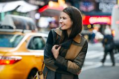 La femme heureuse apprécient la promenade l'horaire d'hiver sur la rue et faire de New York City des achats de Noël images stock