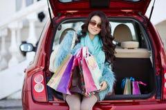 La femme heureuse après l'achat charge votre voiture Photo stock