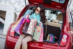 La femme heureuse après l'achat charge votre voiture Image stock
