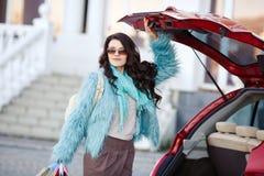 La femme heureuse après l'achat charge votre voiture Image libre de droits