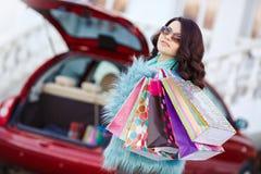 La femme heureuse après l'achat charge votre voiture Photos libres de droits