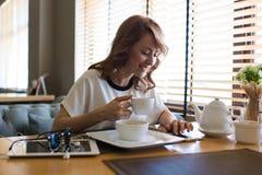 La femme heureuse attirante caucasienne a lu le message textuel à son téléphone de cellules Photos stock