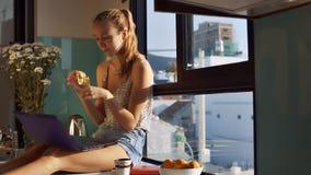 La femme heureuse avec l'ordinateur portable mange la banane sur le rebord de fenêtre banque de vidéos