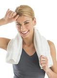 La femme heureuse avec la serviette autour de l'essuyage de cou a sué Images stock
