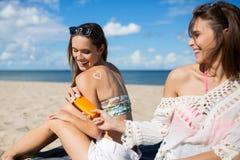 La femme heureuse avec le coeur se connectent se reposer de retour sur la plage avec l'ami Photos stock