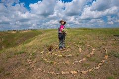 La femme heureuse, avec le petit chien drôle, se tient dans la prairie Photo libre de droits