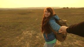 la femme heureuse avec le sac ? dos tient l'homme par la main et le m?ne Les jeunes couples tenant des mains voyagent venez après banque de vidéos