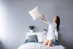 La femme heureuse ayant l'oreiller d'amusement jette apprécier l'activité drôle le week-end à la maison photographie stock libre de droits