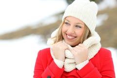 La femme heureuse a chaudement vêtu regarder le côté en hiver image libre de droits