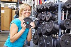 La femme heureuse choisit des charges pour l'haltère dans la boutique de sport Photo libre de droits
