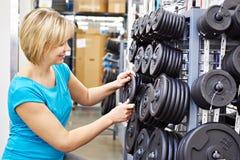 La femme heureuse choisit des charges pour l'haltère dans la boutique de sports Photo libre de droits