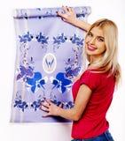 La femme heureuse colle le papier peint. photo libre de droits
