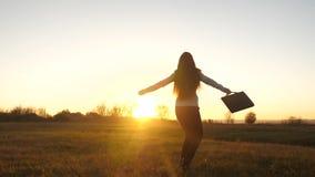 La femme heureuse d'affaires avec la serviette à disposition apprécie le succès au coucher du soleil dans les rayons lumineux du  banque de vidéos
