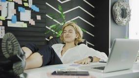La femme heureuse d'affaires a fini son travail Jambes sur la table banque de vidéos