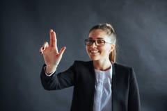 La femme heureuse d'affaires montre le doigt, se tenant sur un fond noir dans le studio, amical, souriant, se focalisent en main photographie stock libre de droits