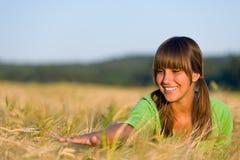La femme heureuse dans le domaine de maïs de coucher du soleil apprécient le soleil Photo libre de droits