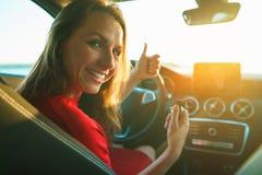 La femme heureuse dans une robe rouge avec une clé dans sa main s'assied dedans photographie stock libre de droits