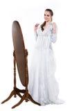 La femme heureuse de Beautifu chosing et essayent la robe de mariage près du miroir Photographie stock libre de droits