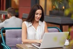 La femme heureuse de brune dans des vêtements blancs s'assied devant l'ordinateur portable ouvert, lit la réponse, reçoit l'email photos libres de droits