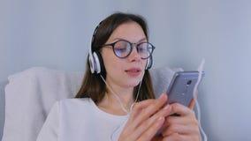 La femme heureuse de brune en verres est musique de écoute dans des écouteurs sur le smartphone et chanter une chanson clips vidéos