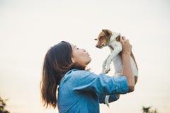 La femme heureuse de hippie sourit et tient un petit chien Petit chiot W Photos libres de droits