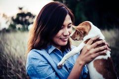 La femme heureuse de hippie sourit et tient un petit chien Petit chiot W Image stock