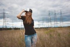 La femme heureuse de jeune énergie porte un hip-hop de chapeau sur le champ jaune avec des pylônes de puissance, grands-angulaire photographie stock