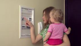 La femme heureuse de mère avec peu de fille de fille allument le levier dans la boite à fusible banque de vidéos