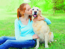 La femme heureuse de propriétaire étreint le chien de golden retriever sur l'herbe Photos libres de droits