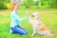La femme heureuse de propriétaire forme le chien de golden retriever sur l'herbe en parc Image libre de droits