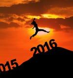 La femme heureuse de silhouette saute au-dessus des numéros 2016 Photo stock