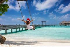 La femme heureuse de voyageur avec le chapeau du père noël s'assied sur une oscillation sur une plage tropicale photos libres de droits